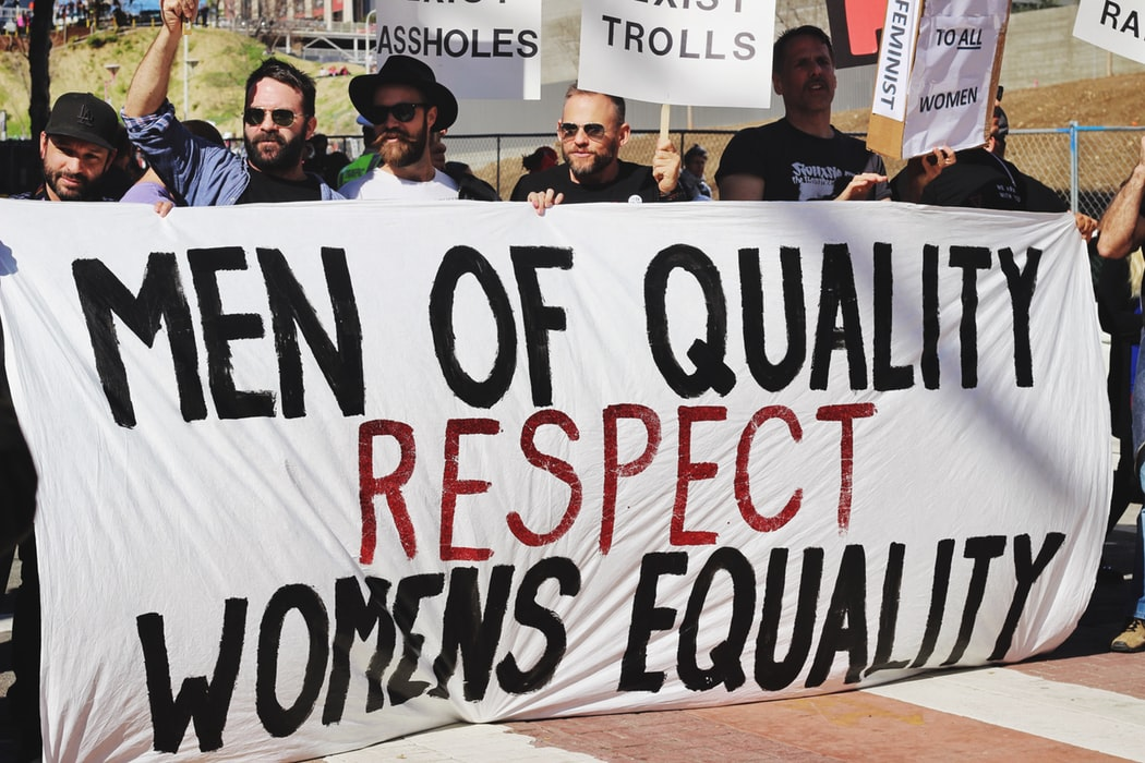 "Men holding a banner written ""Men of quality respect women's equality""."