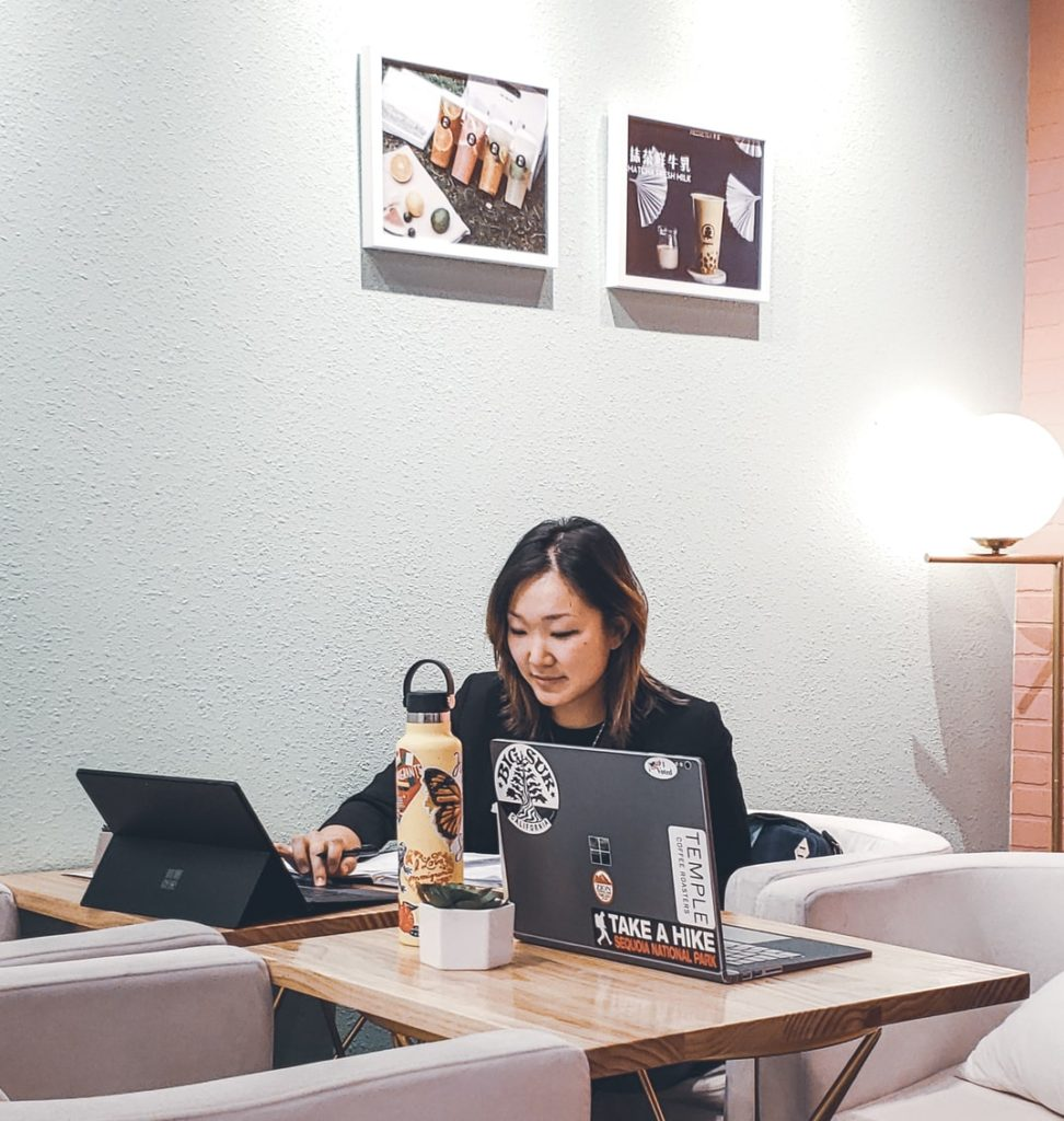 A woman sitting on a chair and working with a laptop on the table