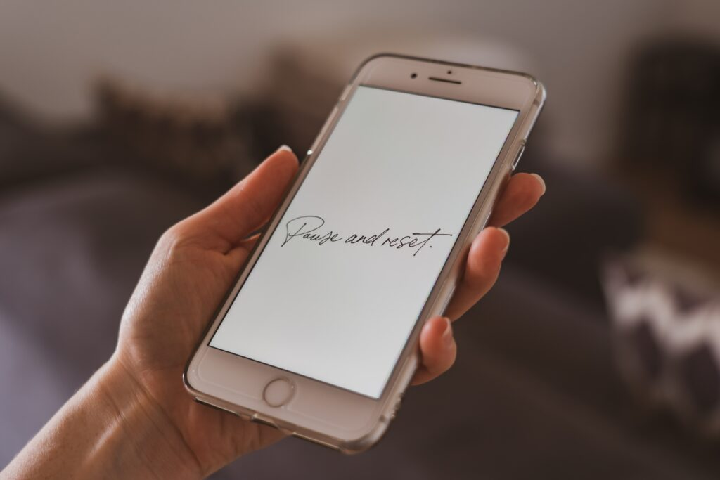 A person holding a silver screen Iphone